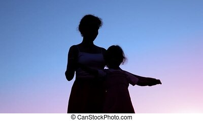 mother holding hands of her little daughter against sunset...