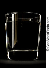 Glass of water on black background