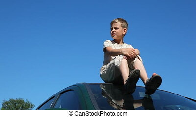 boy sitting on roof of car, pointing to something by hand,...