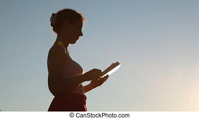 silhouette of woman with book standing against sky