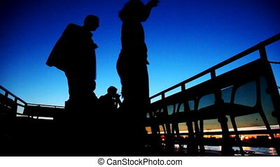 Couple dancing on board ship sailing against sky at night -...