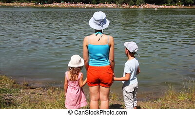 woman with girl and boy standing holding hands turned toward river
