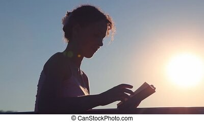 woman turning over the pages and reading book against sunset...