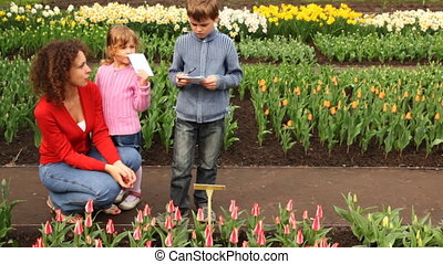 Boy writes information about flowers, near of its mother and sister