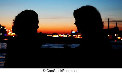 Silhouettes two girls sitting and talking on deck of ship...