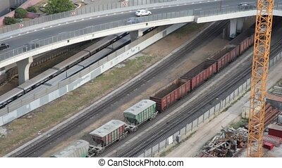 railroad cargo train and cars moving on bridge in city
