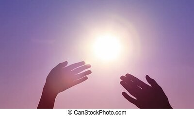 opened palms of man and woman touching against sun