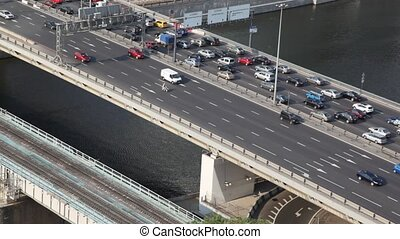 many cars moving on bridge above Moscow river, top view