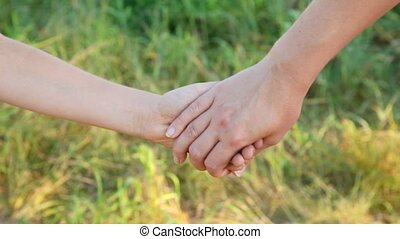 joined hands of woman and boy separating - joined hands of...