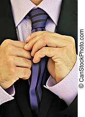 Tie - Details of person straightens his tie for a suit
