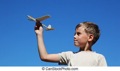 boy holding toy airplane model made of wood against blue sky...