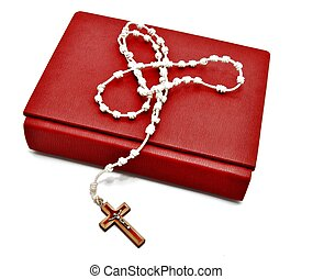 Catholic Rosary on a bible, surrounded by white