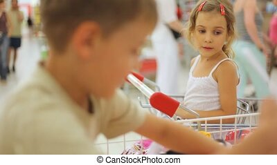 boy and girl in supermarket with clothes - boy and little...
