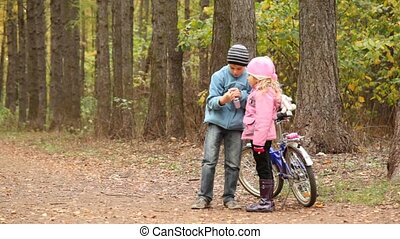 Little girl and boy stand with bicycle in park.