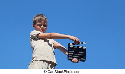 boy stands with clapperboard, shouting, flicks it and sat...