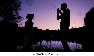 silhouettes of boy and man blowing up soap bubbles