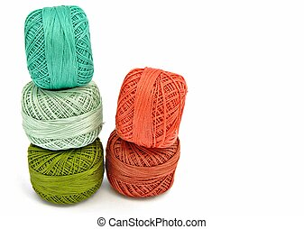 Yarns of different colors next to each other surrounded by...