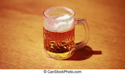 transparent cup of beer standing on wooden table, light and...