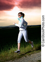 jogging woman - A woman jogging in front of cross country