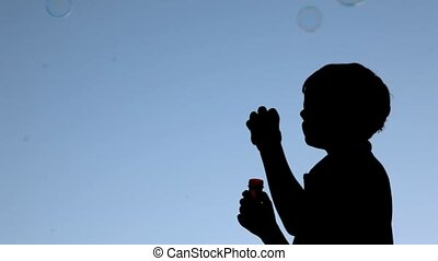 silhouette of boy blowing up soap bubbles