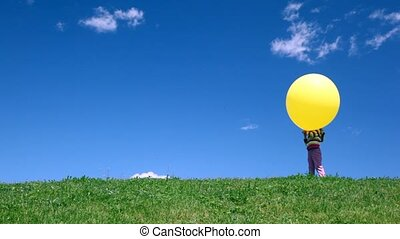 Girl stands with bubble on grass meadow