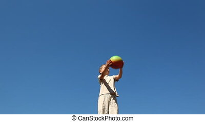boy standing pop-up ball against blue sky - boy standing...