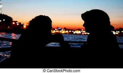Silhouettes two girls sitting and talking on deck of ship -...