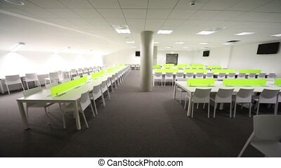 Light room without windows, white elongated tables and...