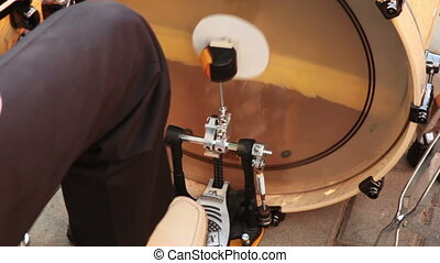 man playing bass drum, pressing his foot on pedal sitting in...