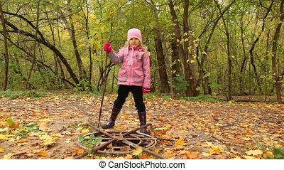 Girl searches for something in the hatch in park. - Little...
