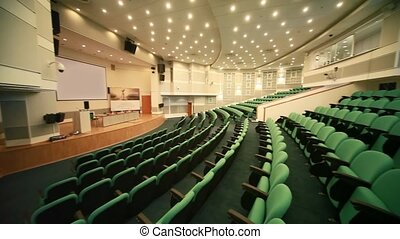 empty conference hall with green seats and big screen
