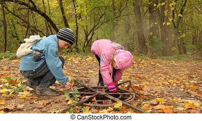 Children search for something in the hatch in park. -...