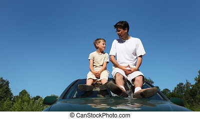 father and son sitting on roof of car talking about...