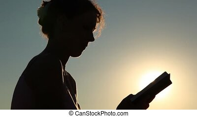 silhouette of woman with book against sun on afternoon sky