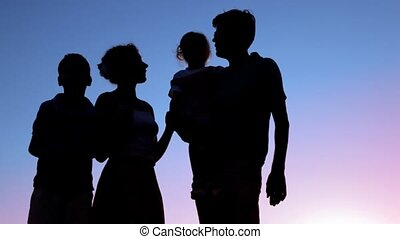 silhouettes of family stands against sky