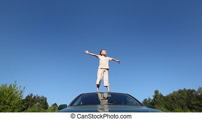 boy stands on roof of passenger car with his hands wide apart