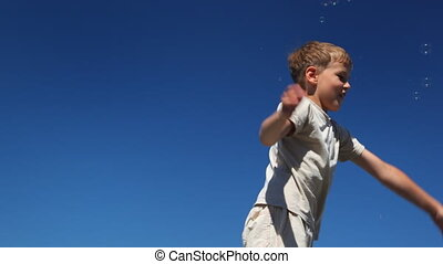 boy waving his arms, knocking lot of flying to him bubbles