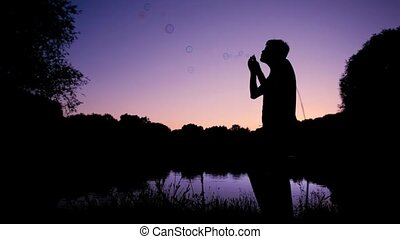 man standing near pond and blowing up soap bubbles