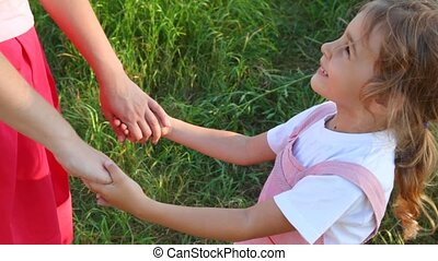 girl and mother have joined hands in park - happy little...