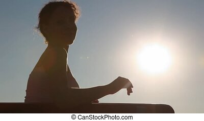woman sitting on bench against afternoon sky with sun