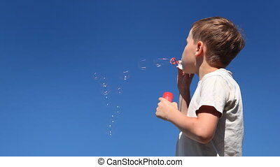 boy blows up lot of bubbles