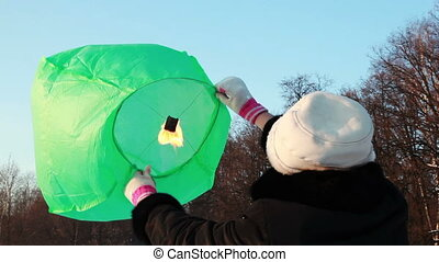 woman standing at winter woods and keeps on wind green chinese lantern inside it lit fire