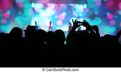 Silhouette of people who look a concert of popular music and...