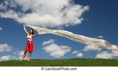 Woman stands with rainbow fabric on grass