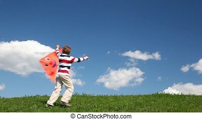 Boy runs with kite in meadow - boy runs with orange kite in...