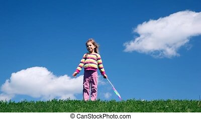Girl stands and playes with wind propeller - girl stands and...