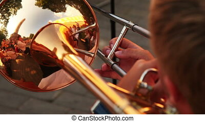 man playing trumpet music sitting on sunny summer day,...