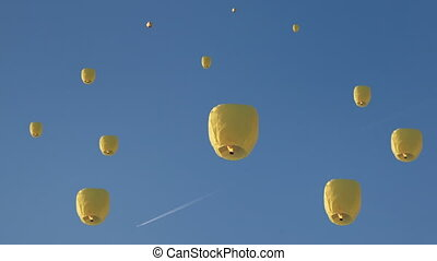 high into blue sky fly chinese lanternes and above them...