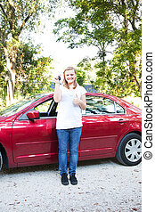 Teen With First New Car - Teenage girl holding the keys to...