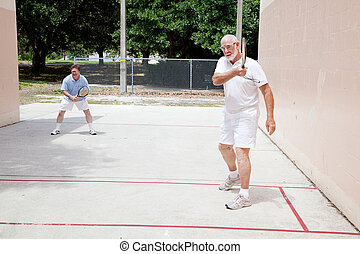 Father Son Raquetball - Fit senior man plays raquetball with...